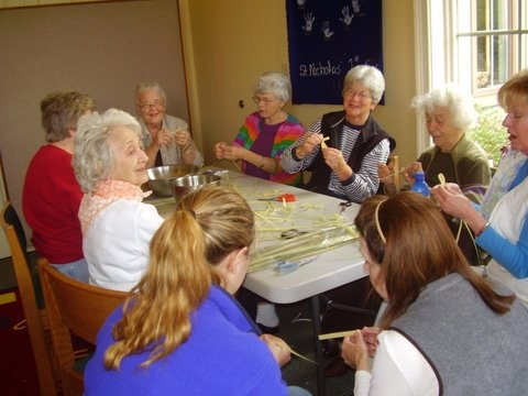 A group of women gather to make Palm Crosses for Palm Sunday.