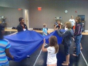 The improv turns to unity as the children surround the cloth.